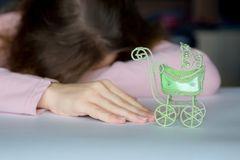 A pose of despair, a loss of hope. A woman lies face down on a table, with cancer reaching for a toy baby carriage. stock images