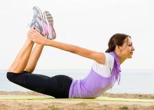 Pose di pratica di yoga della donna che stanno sulla spiaggia Immagini Stock Libere da Diritti
