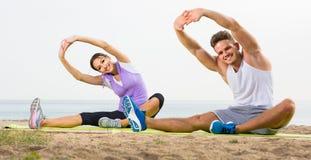 Pose di pratica di yoga della ragazza e del tipo che si siedono sulla spiaggia dal mare al da Fotografie Stock