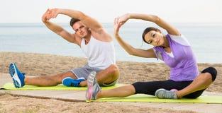 Pose di pratica di yoga della ragazza e del tipo che si siedono sulla spiaggia dal mare al da Fotografia Stock