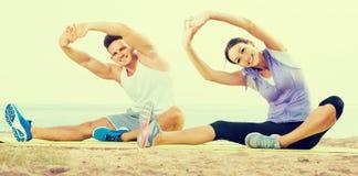 Pose di pratica di yoga della ragazza e del tipo che si siedono sulla spiaggia dal mare al da Immagine Stock Libera da Diritti
