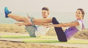 Pose di pratica di yoga della ragazza e del tipo che stanno sulla spiaggia Immagine Stock