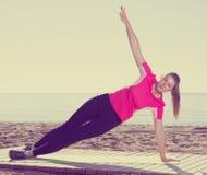 Pose di pratica di yoga della ragazza sulla spiaggia Fotografie Stock Libere da Diritti