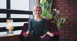 Pose di pratica sorridenti di meditazione di signora di buon umore di yoga a casa sul sofà in un'atmosfera moderna del salone 4K stock footage