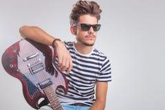 A pose do artista assentou a vista ausente ao descansar a mão na guitarra fotos de stock