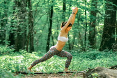 Pose do guerreiro da ioga pela mulher na grama verde no parque em torno do pino Fotos de Stock