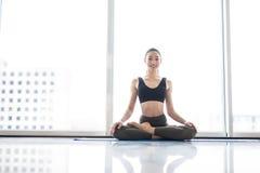 Pose dos lótus da meditação Jovem mulher que pratica a pose flexível da ioga contra janelas panorâmicos no fundo da cidade Imagens de Stock