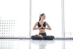 Pose dos lótus da meditação Jovem mulher que pratica a pose flexível da ioga contra janelas panorâmicos no fundo da cidade imagens de stock royalty free