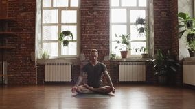 Pose dos lótus da prática do homem no estúdio da ioga com parede de tijolo Homem que faz a pose da ioga vídeos de arquivo