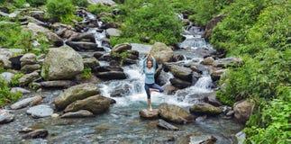 Pose dpoing da árvore do asana da ioga da mulher na cachoeira foto de stock royalty free