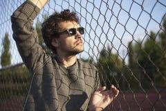 Pose du jeune homme regardant le soleil et tenir la barrière de fer Image stock