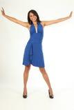 Pose feliz do divertimento pelo vestido azul da rapariga stunning fotografia de stock royalty free