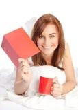 Pose femelle heureuse dans le lit Photo libre de droits