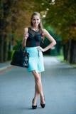 Pose habillée fashoionable de jeune fille en parc Photo stock