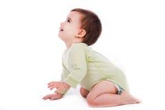 Pose lateral do bebê que senta-se e que olha acima Fotografia de Stock Royalty Free