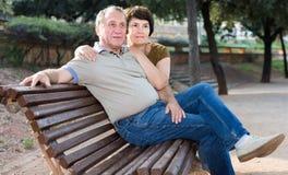 Pose masculine et femelle entre deux âges sur le banc Image stock