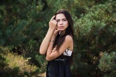 Pose modèle de brune avec du charme gracieuse dans la robe noire en parc conifére Images stock
