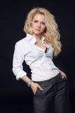 Pose modèle de femme dans la chemise blanche avec la longue OIN bouclée de coiffure photos stock
