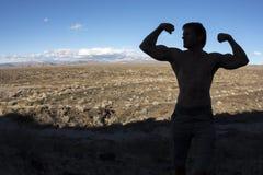 Pose musculaire masculine de silhouette dans le désert Photographie stock libre de droits