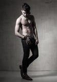 Pose nue supérieure de mode de modèle sexy d'homme dramatique contre le mur grunge photo libre de droits