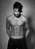 Pose nue supérieure de mode de modèle sexy d'homme dramatique contre le mur grunge Image libre de droits