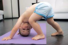 Pose orientée vers le bas de chien par le bébé garçon Images stock