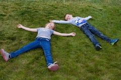 Pose rare de petits enfants sur la pelouse Image libre de droits
