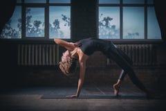 Pose selvagem da coisa do asana desportivo bonito da ioga das práticas da mulher do yogini do ajuste no salão escuro Imagem de Stock Royalty Free