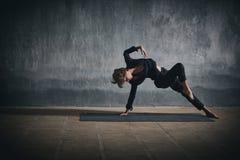 Pose selvagem da coisa do asana desportivo bonito da ioga das práticas da mulher do yogini do ajuste no salão escuro Imagens de Stock Royalty Free