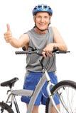 Pose supérieure derrière la bicyclette et renoncer à un pouce Photographie stock