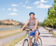 Pose supérieure gaie avec son vélo sur un trottoir Image libre de droits
