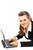 Pose sur la femme d'affaires d'étage à l'aide de l'ordinateur portatif Photo stock