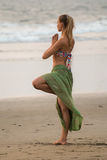 Pose Vrikshasana. A young woman in a bikini is engaged in yoga on the beach. Pose Vrikshasana. Surya Namaskara.  Young beautiful, sexy woman in bikini doing Stock Images