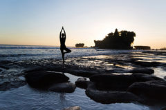 Pose from yoga. Vrikshasana tree pose from yoga by woman silhouette on sunset near Tanah lot temple Royalty Free Stock Photography
