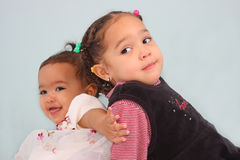 Posed sisters. Back to back pushing each other away Royalty Free Stock Photography