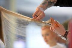 POSEN, POLEN - 7. MAI 2016: Friseur, der blondes Haar w trimmt Lizenzfreies Stockfoto