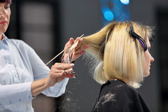 POSEN, POLEN - 7. MAI 2016: Friseur, der blondes Haar w trimmt Stockbild