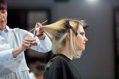 POSEN, POLEN - 7. MAI 2016: Friseur, der blondes Haar w trimmt Lizenzfreie Stockfotos