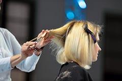 POSEN, POLEN - 7. MAI 2016: Friseur, der blondes Haar w trimmt Lizenzfreie Stockbilder