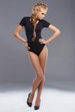 Posera angainstdark för förtjusande och slank blond kvinna Royaltyfri Bild