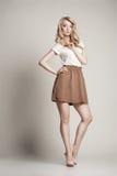 Posera den blonda kvinnan med långt lockigt hår på vit Royaltyfria Bilder