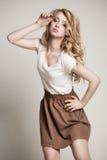 Posera den blonda kvinnan med långt lockigt hår på vit Royaltyfria Foton