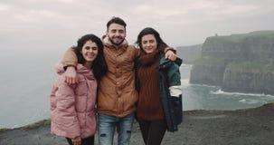 Posera för karismatisk en grabb som och för två dam är roligt för några bilder för minnen på taköverkanten av klipporna, framme stock video
