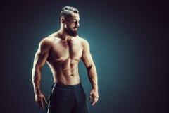 posera för kroppsbyggare Kondition tränga sig in man på mörk bakgrund Royaltyfri Foto