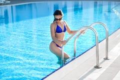 Posera för kvinna som är utomhus- i sommar i bikini på pöl Royaltyfria Bilder