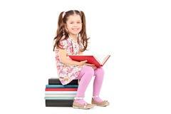 Posera för liten flicka som placeras på en bunt av böcker Fotografering för Bildbyråer