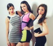 Posera för tre elegant härligt flickor som isoleras på vit Arkivfoto