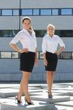 Posera för två ungt attraktivt affärskvinnor som är utomhus- Arkivfoto