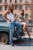 posera för bilflicka som därefter är retro till Arkivfoton