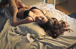Posera i säng Fotografering för Bildbyråer